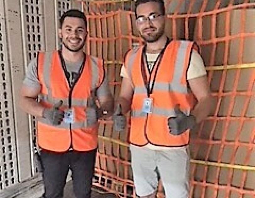 2 Versandmitarbeiter in orangenen Sicherheitswesten stehen auf der Ladefläche eines Lkws. Hinter ihnen: die mit einem Netz gesicherte Päckchen-Beladung.