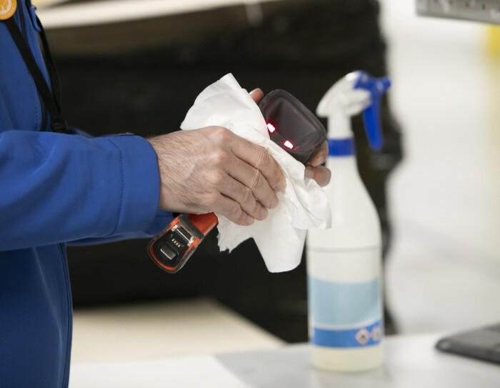 Primer plano de unas manos de hombre limpiando con un pañuelo de celulosa el escáner de mano. De fondo el dispensador de gel hidroalcohólico. Las manos del hombre tienen vello y el asociado lleva una chaqueta de color azul.