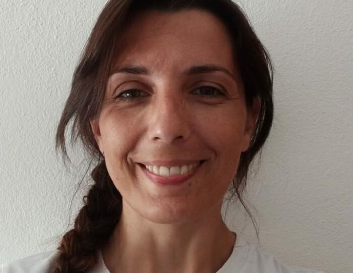 Primo piano della volontaria Amazon Sara. La donna indossa una maglia bianca con un disegno nero, ha i capelli lunghi raccolti in una treccia.