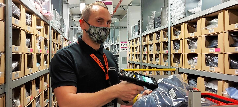 Jens mit schwarzem Poloshirt und Nike-Sporthose sowie in Maske beim Einlagern im Logistikzentrum.