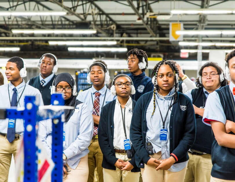 High school students wearing school uniforms and headphones participate in an Amazon fulfillment center tour in Etna, Ohio.