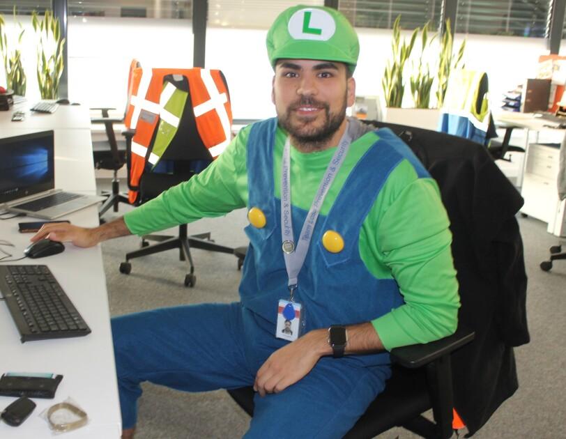 Ein Mann in grünem Shirt und blauer Latzhose.