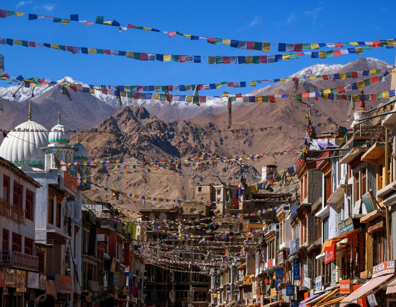 Under a bright blue sky and colorful prayer flags, multi-story buildings with shops are photographed on facing sides of a street. Domed structures and snow-capped mountains are in the background.