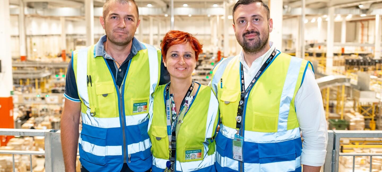 Tre dipendenti Amazon in posa presso il centro di distribuzione di Castel San Giovanni