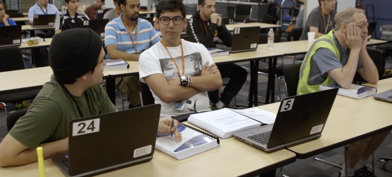 Aula de formación llena de hombres de diferentes edades. En el centro aparece un hombre joven delante de un ordenador y con los brazos cruzados.