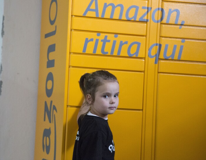 Una bambina davanti all'Amazon Locker Geremia nella Biblioteca di Scampia