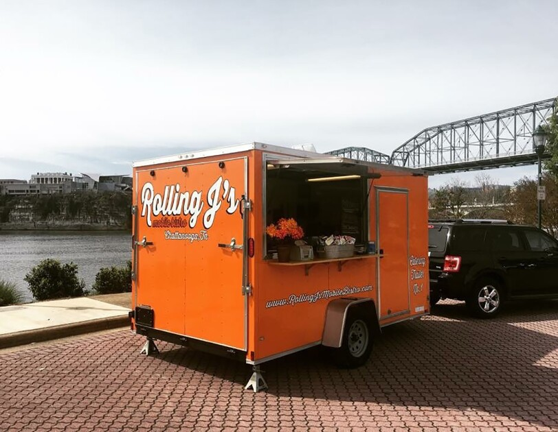 "An orange food truck parked in front of the Tennessee River. The food truck has ""Rolling J's"" branding on it, and is parked on a street made of pavers."