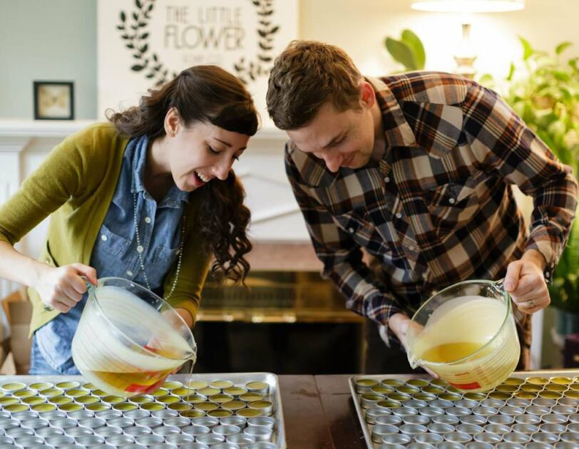 A woman (left) and man (right) hold large measuring cups filled with a liquid and pour the contents into small, metal containers.