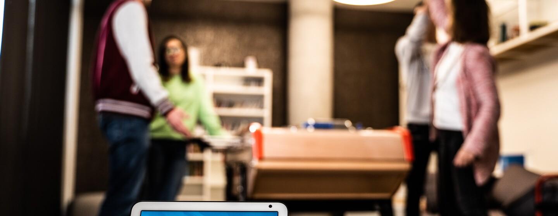 El dispositivo Echo Show en primer plano con la pantalla de color azul la hora y la temperatura. EL dispositivo se encuentra encima de una mesa. De fondo se ven cuatro personas jugando al futbolín. Dos chicos y dos chicas. Las parejas son mixtas y una de ellas se está celebrando que ha marcado un gol.