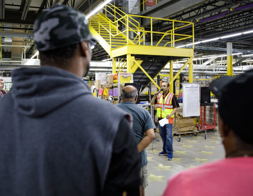 People stand in a warehouse space and look toward a man in a yellow safety vest who is speaking into a microphone.