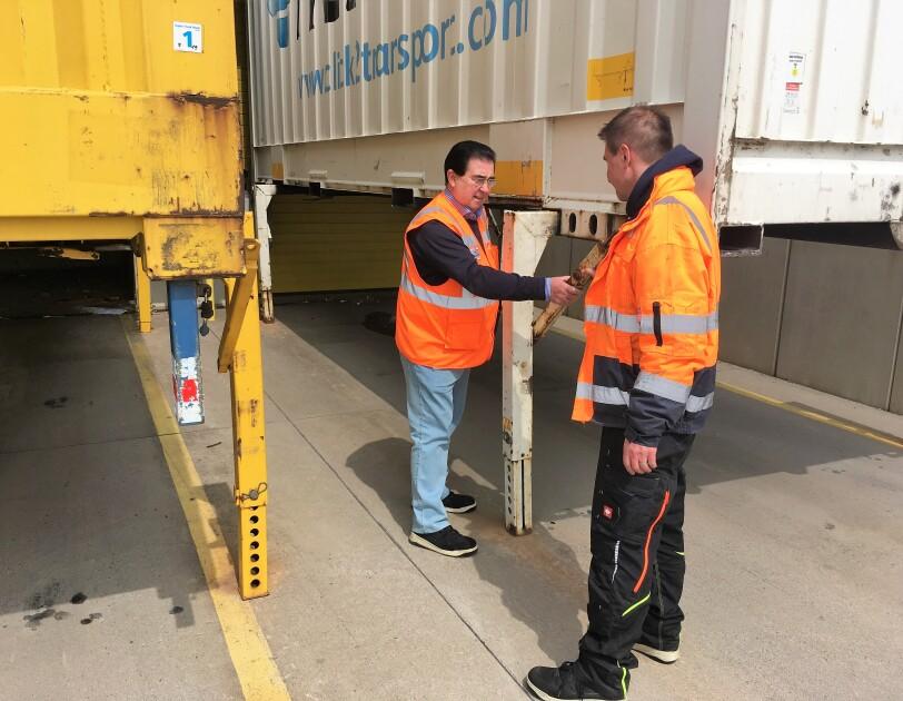 2 Männer in orange-farbenen Sicherheitswesten checken die Stützen einer Lkw-Brücke