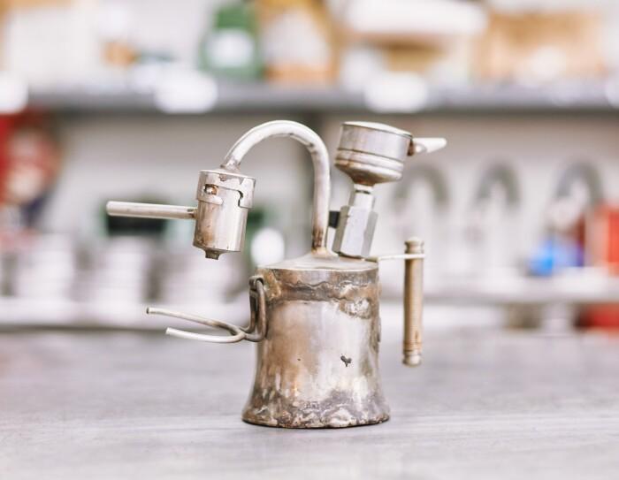 Foto di un prototipo vecchio e piuttosto malandato di caffettiera Kamira, composto da pezzi recuperati da altre caffettiere. Una forcella è attaccata al corpo della caffettiera per reggere la tazzina. Sono molto evidenti le saldature fatte a mano - che questo modello vecchiotto sia esploso durante i test?