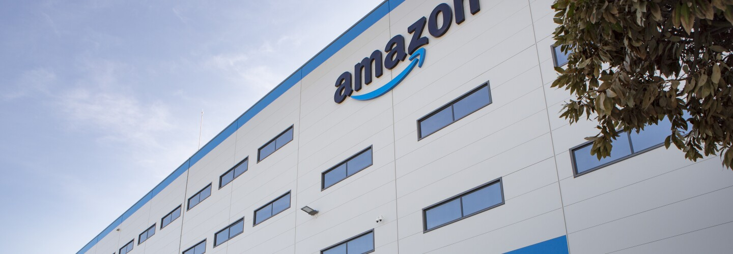 Photo of the Dos Hermanos fulfillment center in Spain, view of the building entrance with Amazon signage.