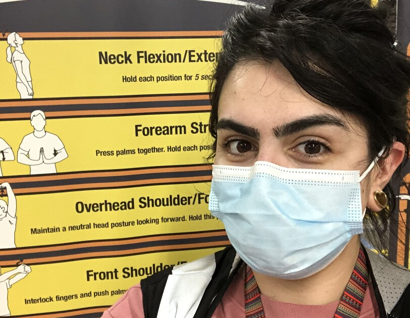 Beka Perez, an Amazon associate, smiles for a photo in front of a sign at an Amazon fulfillment center. The sign shows useful stretches for fulfillment center employees. Beka is wearing a face mask.