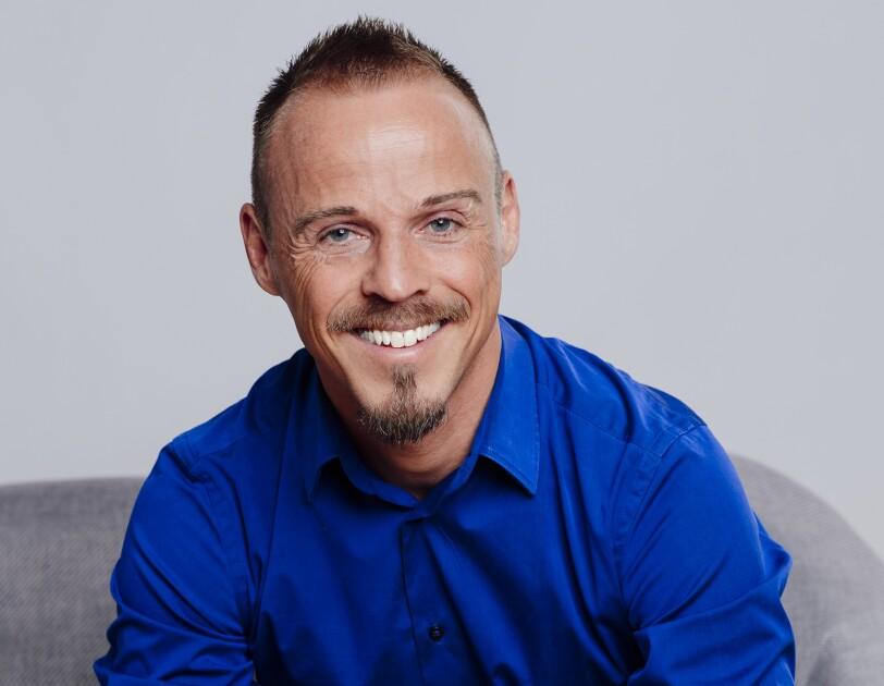Ein Mann mit blauem Hemd und kurzen Haaren lacht in die Kamera.