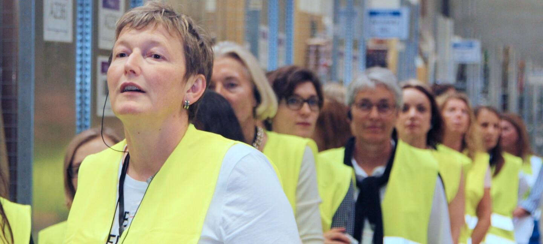 Mehrere Frauen mittleren Alters in gelben Sicherheitswesten stehen hintereinander. Im Hintergrund sind man die Regale des Logistikzentrums.