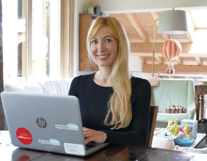 Una donna è seduta ad un tavolo e ha davanti a sè un PC. Indossa una maglia nera e ha i capelli biondi. Alle sue spalle si intravede il salotto di un appartamento, sulla sinistra c'è una porta-finestra.