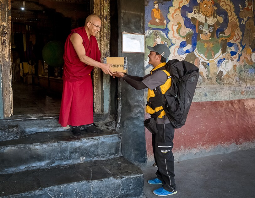 A Buddhist monk in glasses and maroon-colored robes accepts an Amazon package from a uniformed delivery associate. The associate stands at street level and is flanked by a colorful mural. The monk stands in a doorway on the second of three steps that lead into the building behind him.
