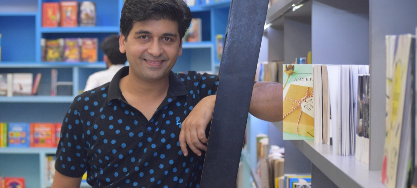 Ajay Pandey poses next to a book shelf