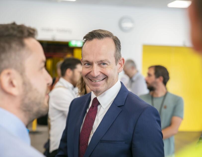Ein Herr im blauen Anzug und rostroter Krawatte blickt lächelnd zum Standortleiter, den man etwas unscharf und im Seitenprofil sieht
