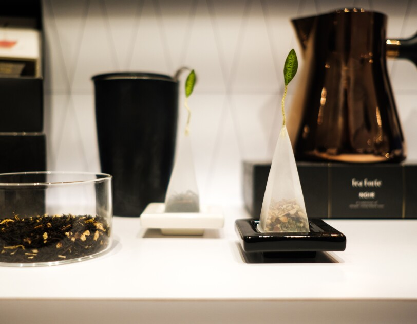 Loose tea leaves in a clear glass container next to two pyramid-shaped teabags.