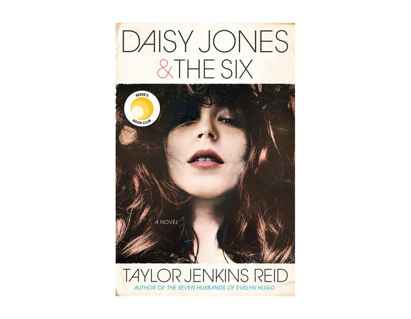 "A book cover for ""Daisy Jones & the six,"" a novel by Taylor Jenkins Reid shows a young woman with long dark hair looking downward into the camera. The book background is an age-stained ivory, with all-caps font for the title and author's name."