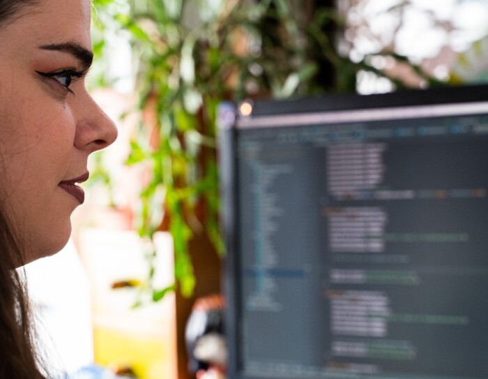 Primer plano de Violeta González. Se le ve los labios y los ojos maquillados y solo un mechón de pelo. Desenfocado una pantalla de ordenador y detrás una planta.