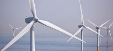 Wind turbines standing in ocean waters.