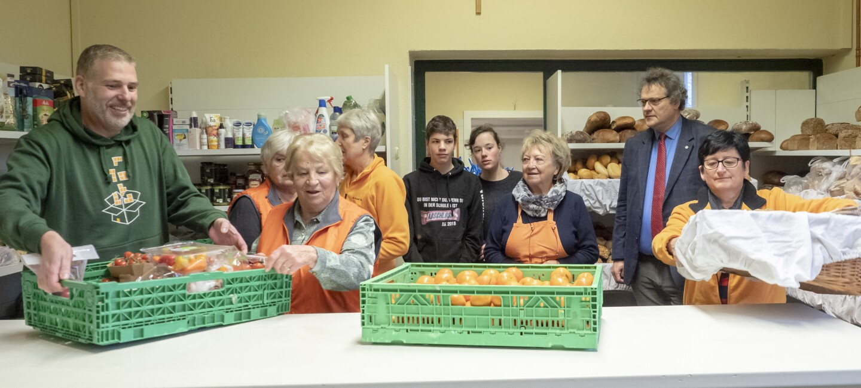 Verschiedene Helfer stellen die Waren für die Ausgabe der Lebensmittel bereit
