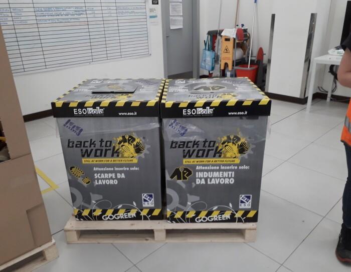 Due scatole di cartone poggiate su un pallet fungono da cestino per inserire indumenti e scarpe da lavoro che verranno poi riciclati. Sulle scatole è scritto 'Back to work'