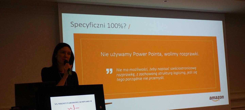 Prelegentka Amazon z mikrofonem, w tle slajd prezentacji z napisem: 'Nie używamy Power Pointa, wolimy rozprawki'