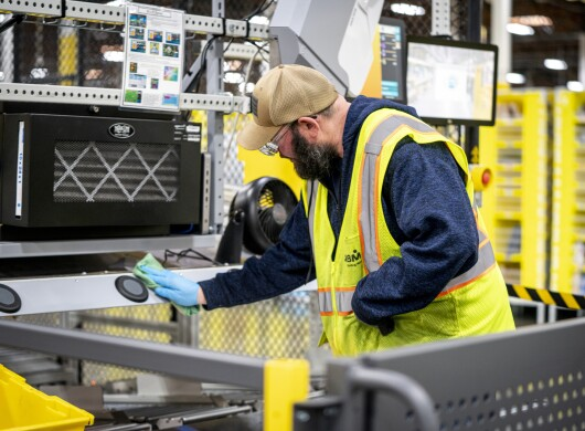 A man wipes down a workstation at an Amazon fulfillment center.