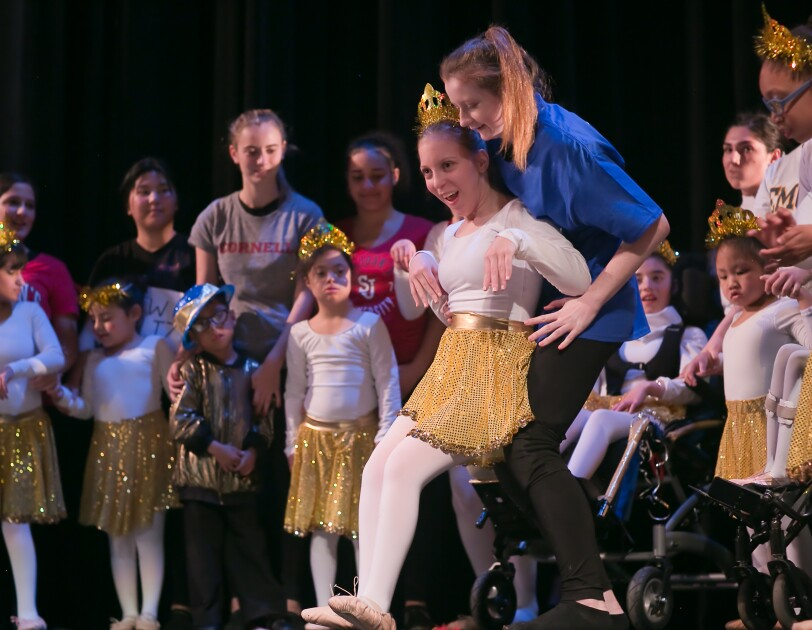 A dancer wearing ballet slippers, a gold skirt, a tiara, and a white leotard and tights performs. The dancer has cerebral palsy and is leaning back against a helper for support. Other dancers and helpers are in the background.