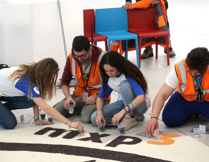 Dipendenti Amazon seduti in terra disegnano il logo MXP3 con il riso nero e arancione