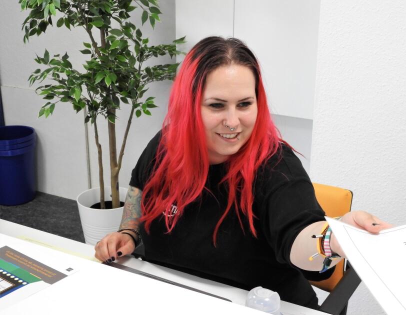 Eine langhaarige Frau mit roten Haaren sitzt an einem Schreibtisch und reicht gerade Unterlagen weiter. Sie lächelt. Das ist Bentje Schoop, Hiring Assistant bei Amazon.