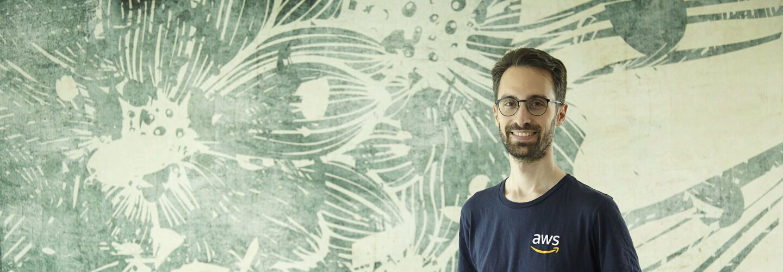 Mezzo busto di Alex Casalboni. Il ragazzo indossa una t-shirt blu con il logo AWS a destra, e un paio di occhiali. Sorride verso la camera. Sullo sfondo, una carta da parati beige e verde.