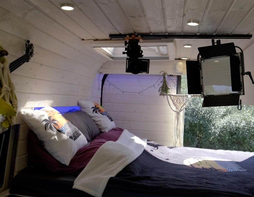 Innenansicht des Camper Vans mit Bett und Fernseher.