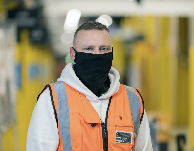 Marcin Jeznach wearing a mask and high-vis jacket in an Amazon Fulfilment Centre.