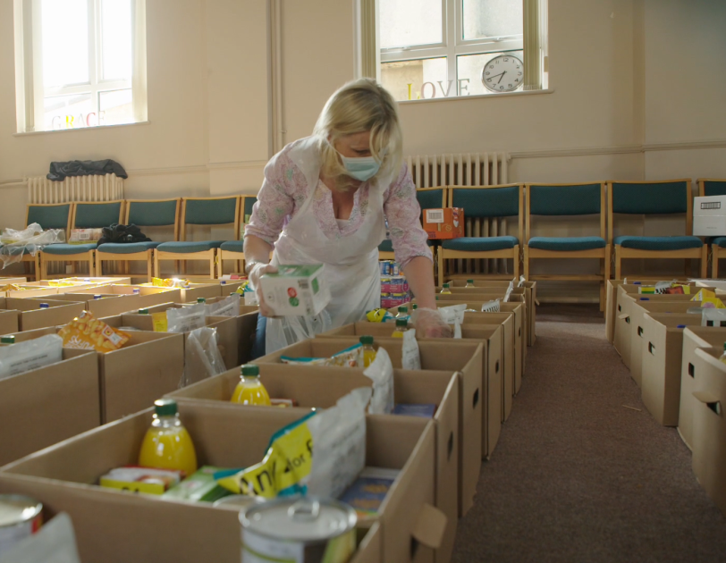 A lady packing boxes of food to provide as FBA donations, she is wearing PPE and there are rows of boxes.
