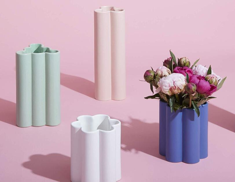 Four shaped vases in varying heights and width. The tallest vase is pink and has a three-petal shape, aqua is slightly smaller and has a bubbly triangular shape, blue is slightly smaller and a six-petal shape, white is shortest and also has a six-petal shape.