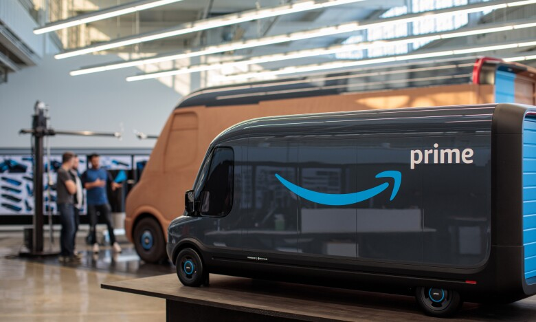 A scale model of a delivery vehicle with the Amazon smile logo. A larger clay model of the vehicle is in the background.