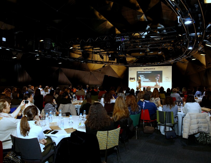 Back of the room point of view of women listening to the conference
