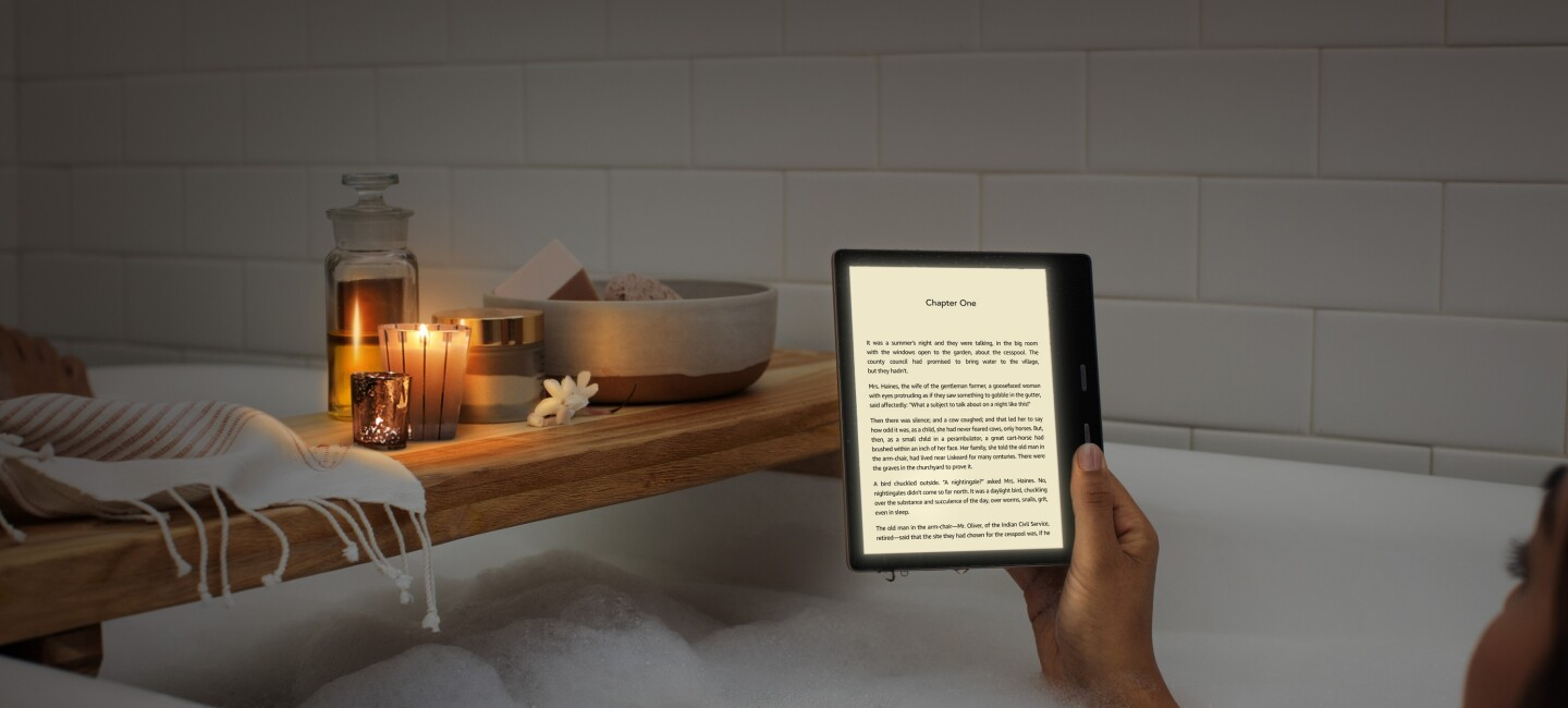 A woman reading an all-new Kindle Oasis in the bath by candle light