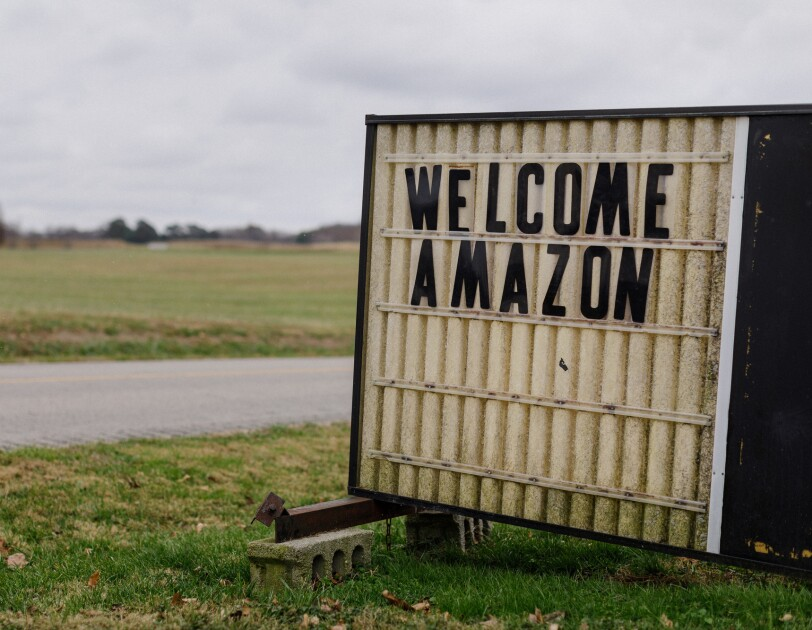 The message 'WELCOME AMAZON' is displayed on a sign balanced atop cinder blocks sitting on a lawn. In the background of the image, there's a road and a grassy field.