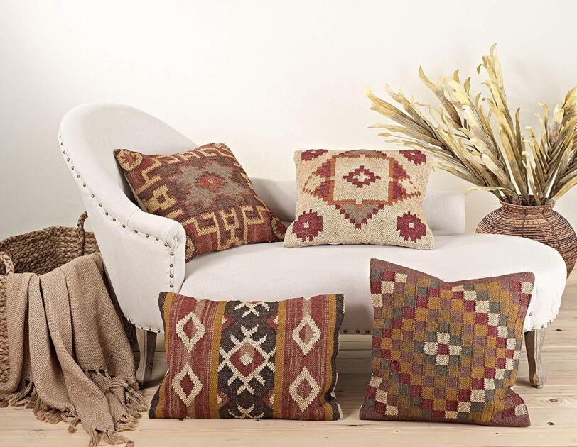 Four kilim-patterned pillows in earth tones rest on and around a chaise lounge. A basket with a cocoa fringe blanket sits to the left of the chaise, and a woven planter with decorativ dried branches sits to the right.