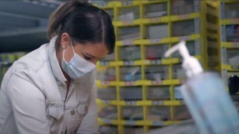 Sicherheit bei Amazon_Eine Mitarbeiterin trägt Mundschutz. Im Vordergrund sieht man eine Flasche Desinfektionsmittel.