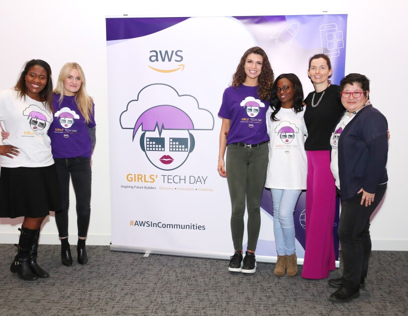 AWS InCommunities - Participating ladies and representatives of AWS standing in front of the AWSInCommunities Girls' Tech Day roll-up at an AWS InCommunity event