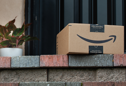 An Amazon package sits on a brick doorstep near a plant.