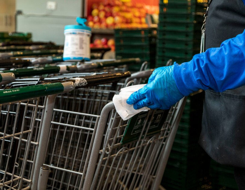 A person wearing gloves uses a sanitizing wipe on a grocery cart.