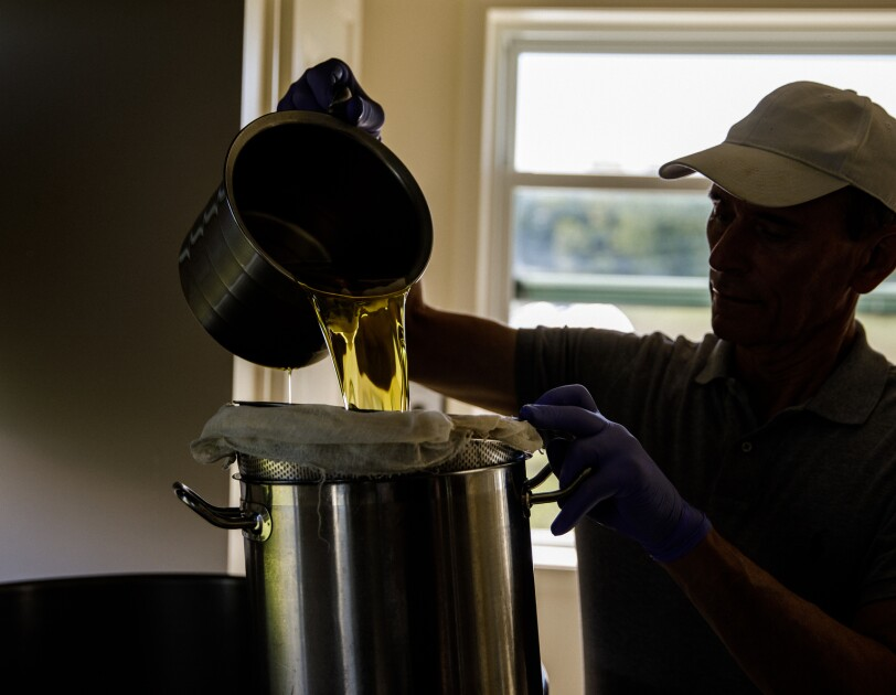 A man pours a liquid from a metal pitcher.